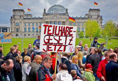 """Demoschild mit Text """"Teilhabegesetzt jetzt!"""" vor dem Berliner Reichstag."""