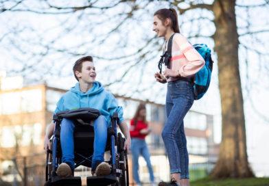 Schüler im Rollstuhl spricht mit Schülerin auf dem Schulhof.
