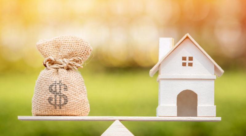 Geldbeutel und Haus auf die Waage gestellt
