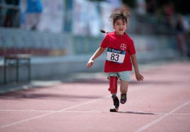 Kind läuft auf Tartanbahn.