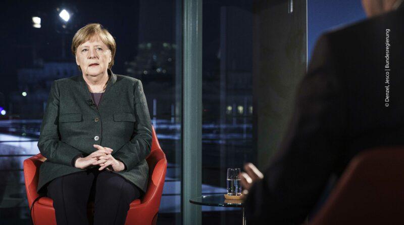 Angela Merkel sitzt auf einem roten Stuhl in einem Fernsehstudio am Abend.