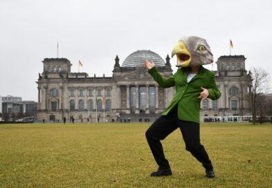 Mensch mit Adlerkopf vor dem Reichstag in Berlin.