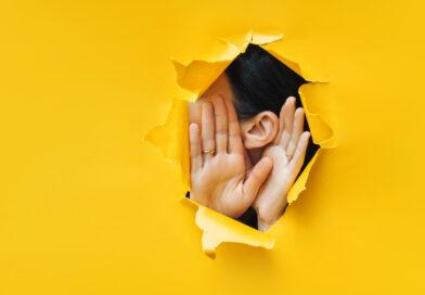 Gelbe Wand mit Loch. Dort ist ein Ohr und zwei Hände zu sehen.