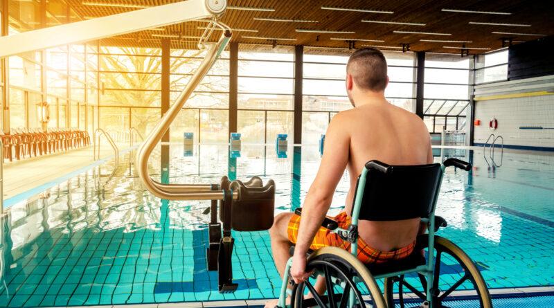 Junger Mann mit Rollstuhl im Schwimmbad mit Liter.